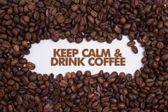 Предпосылка сделанная из кофейных зерен с ` сообщения держит затишье & выпивает ` кофе Стоковое Изображение