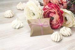 Предпосылка с печеньями пионов, подарочной коробки и меренги на деревянном Стоковая Фотография RF