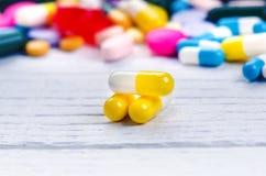 Предпосылка фармации на белой таблице Таблетки на белой предпосылке Пилюльки Медицина и здоровая капсулы закрывают вверх Differen Стоковые Изображения
