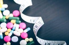 Предпосылка фармации на черной таблице с измеряя лентой таблетки предпосылки черные Пилюльки Медицина и здоровая пистолет конца к Стоковая Фотография
