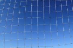 Предпосылка футбола сетчатая с голубым небом Стоковая Фотография
