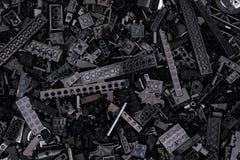 Предпосылка черных блоков, кирпичей и частей Lego Стоковое Фото