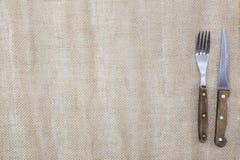 Предпосылка для меню Скатерть холста и нож вилки и стейка Использует для того чтобы создать меню для стейкхауса Стоковое Изображение