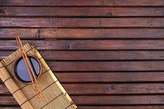 Предпосылка для суш Бамбуковая циновка, соевый соус, палочки на деревянном столе Космос взгляд сверху и экземпляра стоковые изображения