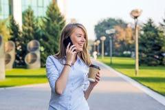 предпосылка blured детеныши женщины городской улицы smartphone гуляя В предпосылке запачканная улица, смотря в фронте Стоковое Изображение RF