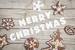 Предпосылка Christmassy серая деревянная с пряником и веселым письмом ` s Christma Стоковые Изображения