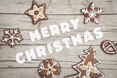 Предпосылка Christmassy серая деревянная с пряником и веселым письмом ` s Christma Стоковое фото RF