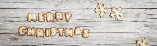 Предпосылка Christmassy серая деревянная с пряником и веселым письмом ` s Christma Стоковое Изображение RF