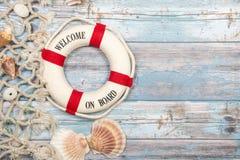 Предпосылка Nautica с томбуем безопасности с гостеприимсвом текста на seashells и рыболовной сетью на backgrou голубых лесов дере Стоковое Фото