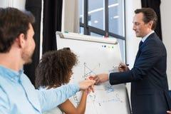 Предприниматели гонки смешивания имея представление на диаграмме сальто пока встречающ обсуждение, бизнесмена и женщину связи Стоковые Изображения RF