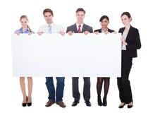 Предприниматели держа пустую доску Стоковые Изображения