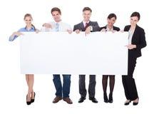 Предприниматели держа пустую доску Стоковое фото RF