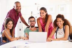 Предприниматели используя компьтер-книжку в офисе начинают вверх дело стоковые фотографии rf