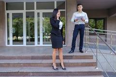 Предприниматели, милая маленькая девочка используют телефон и мальчик носит папку Стоковое Фото