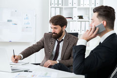 Предприниматели на телефоне делая примечания Стоковое Изображение