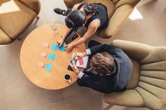 Предприниматели обсуждая над слипчивыми примечаниями в офисе лоббируют Стоковые Фото