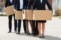 Предприниматели при картонные коробки стоя в линии Стоковое Изображение