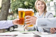 Предприниматели провозглашать стекла пива на внешнем ресторане Стоковое фото RF
