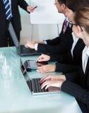 Предприниматели работая на компьтер-книжках и таблетках Стоковое фото RF