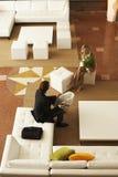 Предприниматели связывая пока сидящ в лобби офиса Стоковое Изображение