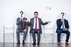 Предприниматели сидя в очереди и ждать интервью, держа вопросительные знаки в офисе стоковые изображения rf