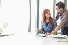 Предприниматели смотря один другого пока работающ на столе в творческом офисе Стоковое Фото