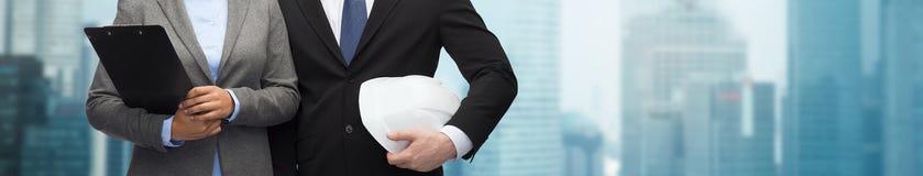 Предприниматели с доской сзажимом для бумаги и шлемом Стоковая Фотография