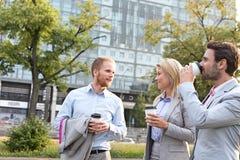 Предприниматели с устранимыми чашками беседуя в городе Стоковые Фото