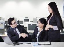 Предприниматели тряся руки в комнате офиса Стоковые Фотографии RF