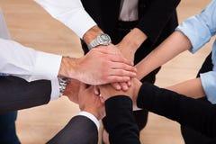 Предприниматели штабелируя их руки Стоковые Фотографии RF