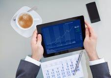 Предприниматель анализируя диаграмму на таблетке цифров в офисе Стоковые Фото