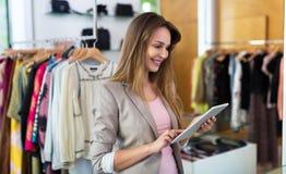 Предприниматель бутика используя цифровую таблетку Стоковая Фотография RF