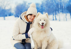 Предприниматель женщины обнимая белую собаку Samoyed на снеге в зиме Стоковое Фото