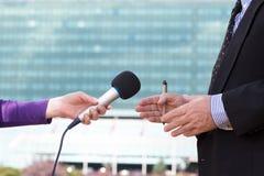 Предприниматель журналиста интервьюируя, корпоративное здание в предпосылке Стоковое Фото
