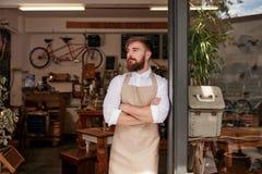 Предприниматель кафа стоя в входе его кофейни стоковое изображение rf