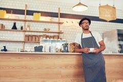 Предприниматель кафа стоя на счетчике с чашкой кофе стоковые фото