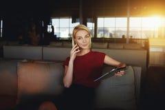 Предприниматель молодой женщины говоря на мобильном телефоне пока ждущ ее заказ в ресторане во время пролома, Стоковые Изображения
