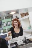 Предприниматель принимая оплату в салоне парикмахерских услуг стоковая фотография rf