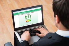 Предприниматель проверяя онлайн показатель кредитного рейтинга на компьтер-книжке стоковая фотография