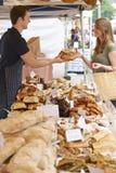 Предприниматель стойла хлеба на клиенте сервировки рынка с хлебцем Стоковое Изображение