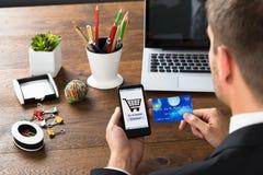 Предприниматель с кредитной карточкой и мобильным телефоном Стоковое Изображение