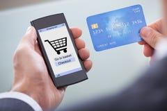 Предприниматель с мобильным телефоном и кредитной карточкой Стоковое фото RF