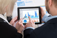 2 предпринимателя анализируя диаграмму на таблетке цифров Стоковые Фотографии RF