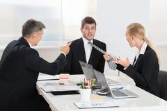 2 предпринимателя враждуя к молодому бизнесмену Стоковое фото RF