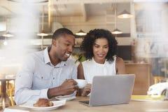 2 предпринимателя встречают в кофейне снятой через окно стоковая фотография