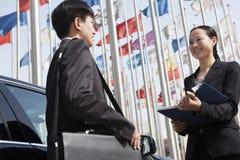 2 предпринимателя встречая outdoors с флагштоками в предпосылке. Стоковые Изображения