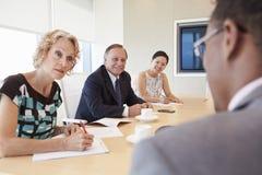 4 предпринимателя имея встречу в зале заседаний правления Стоковое фото RF