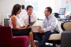 3 предпринимателя имея встречу в лобби гостиницы Стоковые Фотографии RF