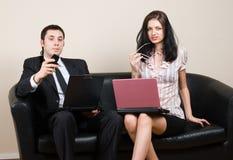 2 предпринимателя используя компьтер-книжки, сидя на софе Стоковые Изображения