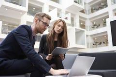 2 предпринимателя используя компьтер-книжку в лобби современного офиса Стоковая Фотография RF